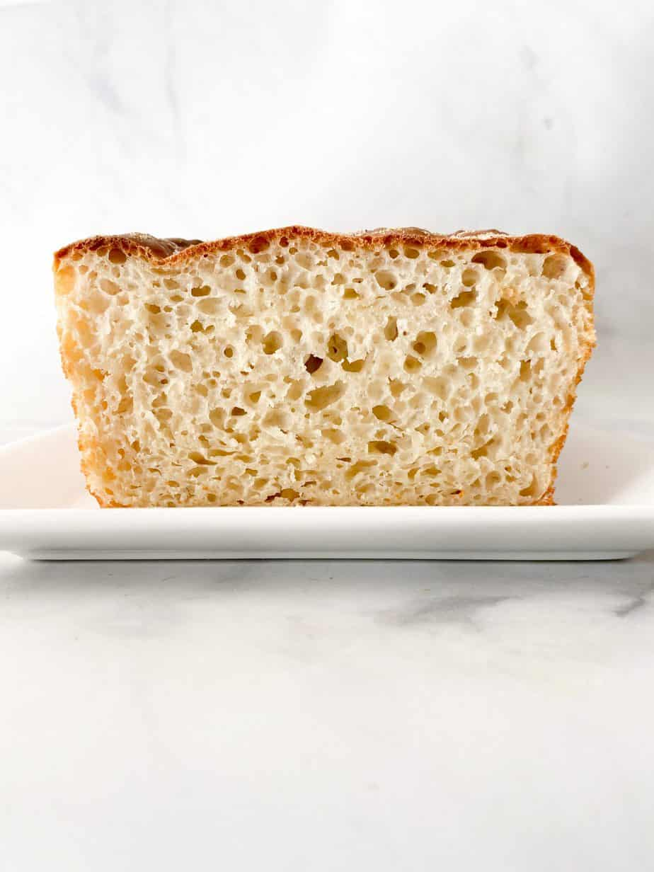 Sliced english muffin loaf on a plate with nooks and crannies