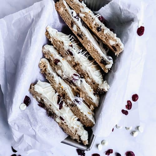 tray of cranberry white chocolate cookie bars with craisins and white chocolate chips around it